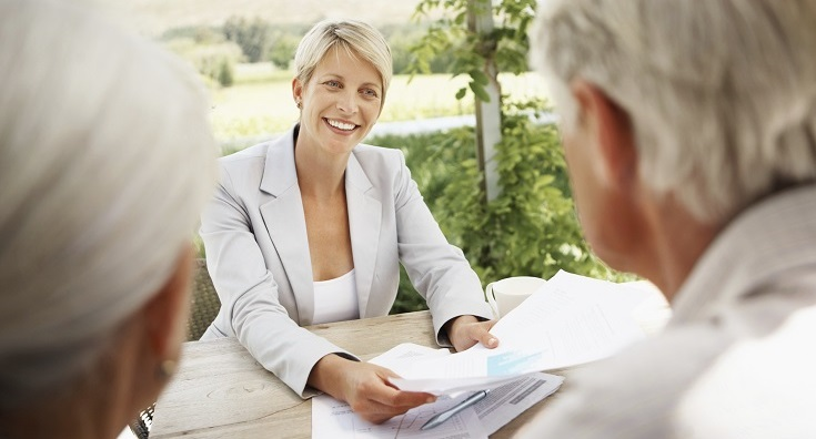 Female real estate agent sitting at a table with a senior couple , discussing property